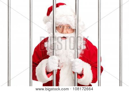 Studio shot of Sana Claus standing behind bars in jail and looking at the camera isolated on white background