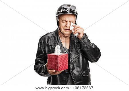 Disappointed senior biker in a black leather jacket holding a box of wipes and crying isolated on white background