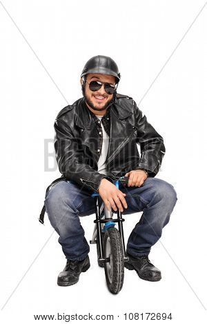 Vertical shot of a male biker in black leather jacket sitting on a small bike and looking at the camera isolated on white background