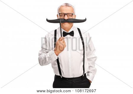 Elegant mature man with a black suspenders and bow-tie holding a fake mustache above his lips and looking at the camera isolated on white background