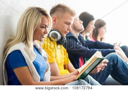Group of students on a break reading books and using smartphones. Focus on a happy teenage girl. Background is blurry.