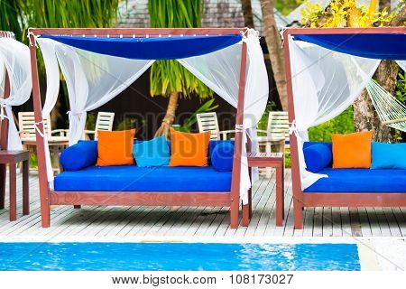 Blue towels on beach beds near swimming pool at tropical resort