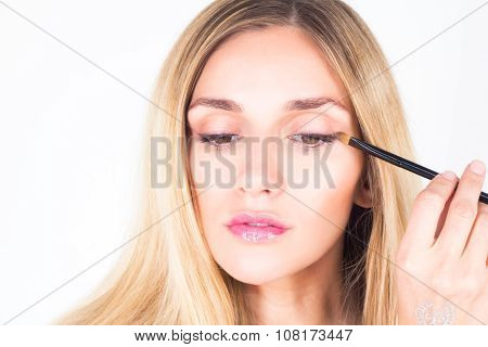 Beautiful woman looking down and apply shade on eyelid