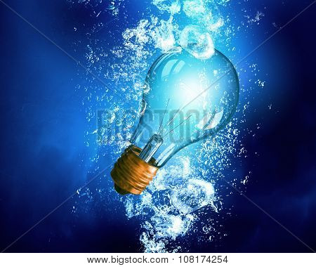 Energy concept with light bulb under clear blue water