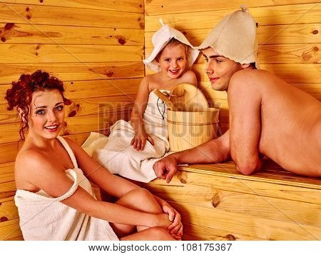 Happy family with child  in hat  relaxing at sauna.