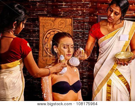 Woman having ayurvedic massage with pouch of rice amoung Indian beauticians.