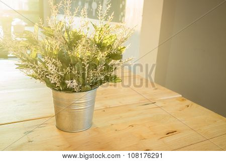 Simply Plant Bucket Decorated On Wooden Table