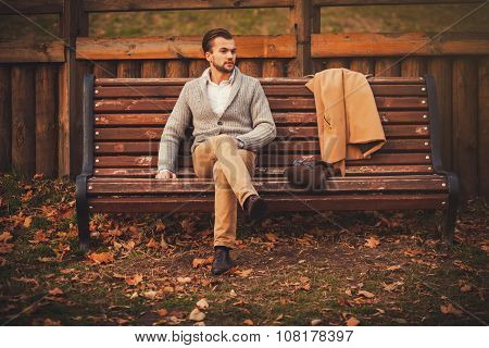 Handsome Young Man Sitting On The Bench