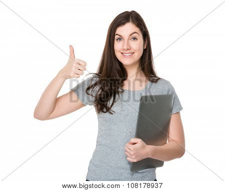 Brunette woman hold with notebook computer and thumb up gesture