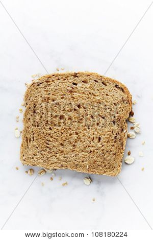 Slice of a whole wheat bread on white marble background