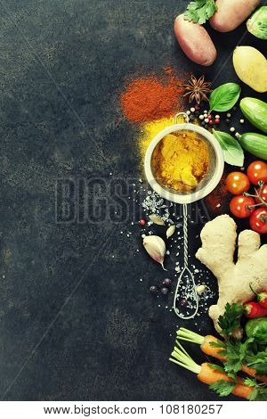 Herbs and spices selection (turmeric, paprika, basil, salt, papper) on dark rustic background. Background layout with free text space.