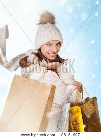 lovely woman with shopping bags on abstract winter background