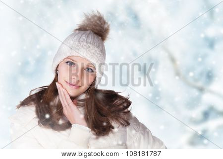 Beautiful winter portrait of young brunette woman in the winter snowy scenery