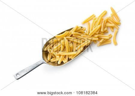 uncooked pasta caserecce in metal scoop on white background