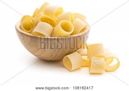uncooked pasta calamarata in bowl on white background