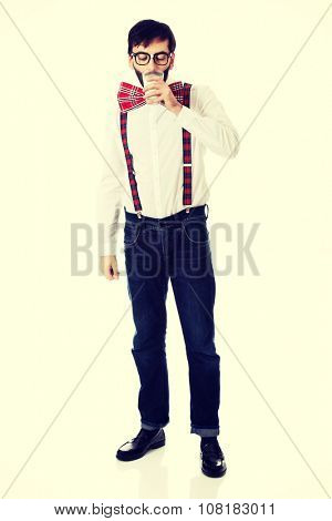 Funny man wearing suspenders drinking milk.