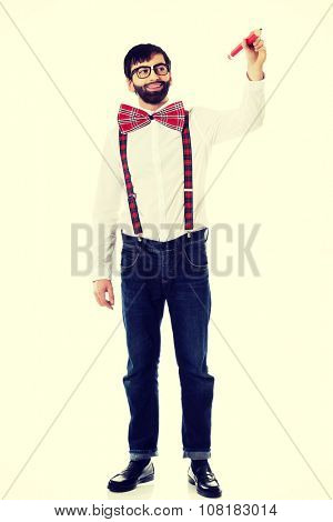 Man wearing suspenders writing with big pencil on space.