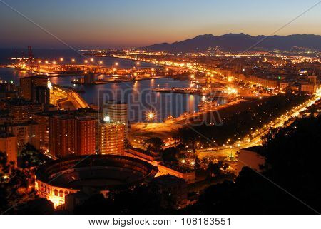 Malaga port and bullring at night.