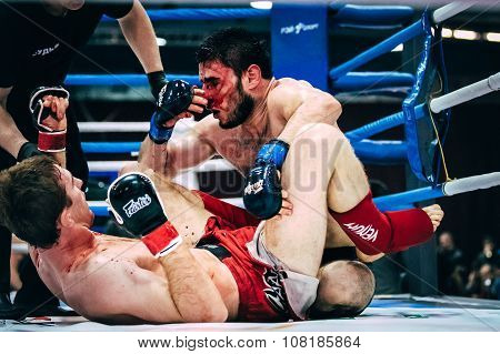 two athletes MMA ground fighting, one of athletes bloody wound
