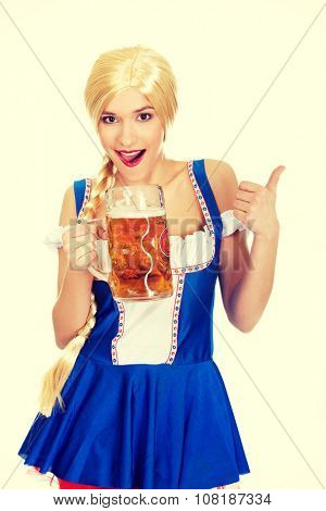 Happy bavarian woman with beer and thumbs up.