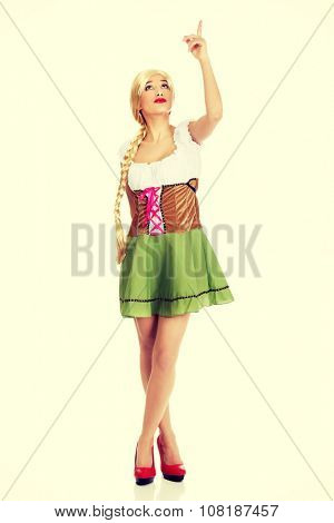 Woman wearing traditional Bavarian dress pointing up.