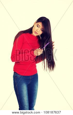 Beautiful woman combing her tangled hair.