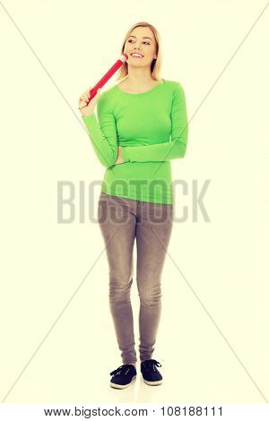 Beautiful thoughtful woman with oversized pencil.