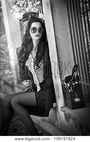 Attractive young woman with sun glasses in autumnal fashion shot. Beautiful lady in black and white