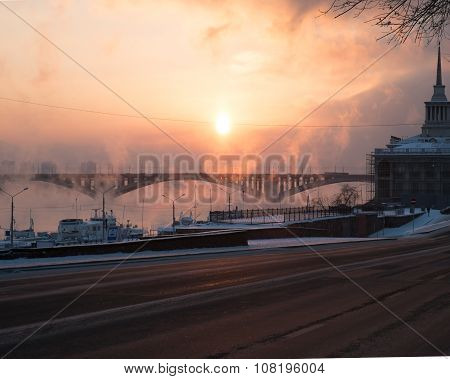 Frosty sunset with steam from the river