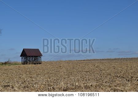 old corn crib sitting at the edge of a field