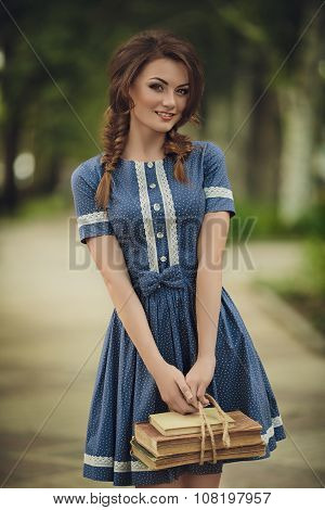 Young girl with old books in vintage dress