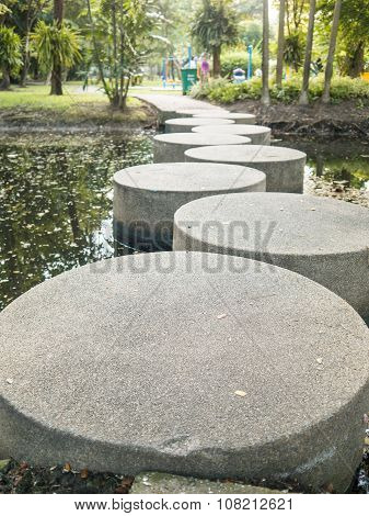 Stone Walkway Across The River In The Park.