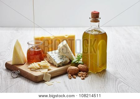 Four Cheeses With Supplements On Chopping Board An White Wooden Table Side View