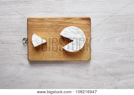 Camembert Pacman Style Isolated On Chopping Board Top View White Brushed Table