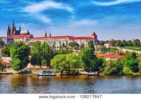 View Of Prague Castle From Waterfront- Famous Historic Bridge That Crosses The Vltava River In Pragu