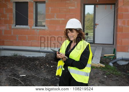 Mature Female Architect Or Construction Engineer On Building Site Supervising, Wearing Hardhat, With