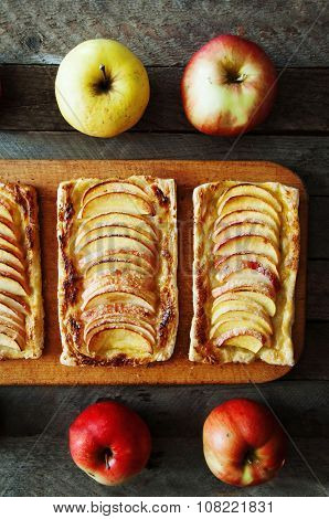 Homemade organic ruddy pies with apples puff pastry, ready to eat. Delicious apple puff on a wooden
