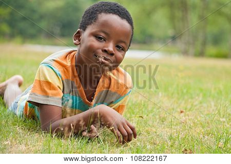 African Boy Eating Grass