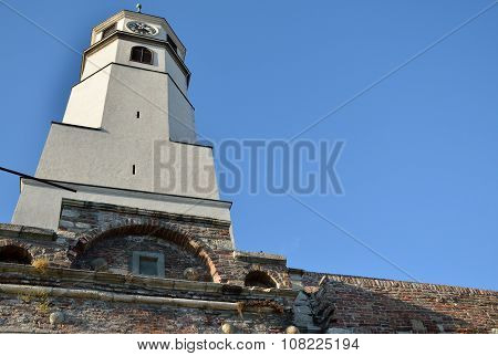 Clock Tower On Brick Walls With Blue Sky
