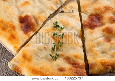 Top view of calzone pizza or ossetian chicken pie with slice and thyme macro close up