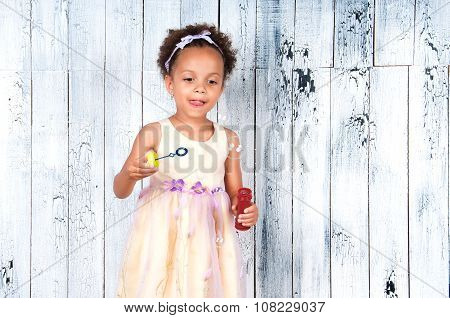 Happy Smiling African  Girl Blowing Soap Bubbles On The Background Of Wooden Wall