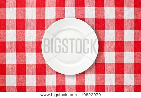 Orange Plate On Red Checked Tablecloth