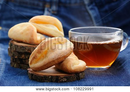 Homemade Cookies And Black Tea On Wooden Stands On Deep Blue Cloth