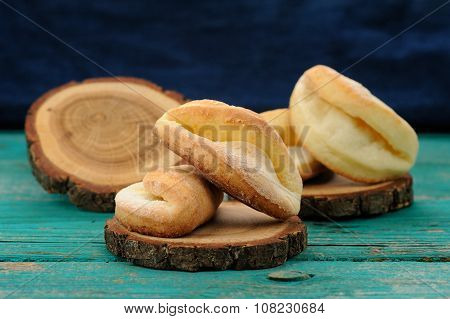Homemade Puff Cookies On Wooden Stands On Turquoise Table