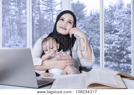 Mother Daydreaming While Working And Nursing Baby