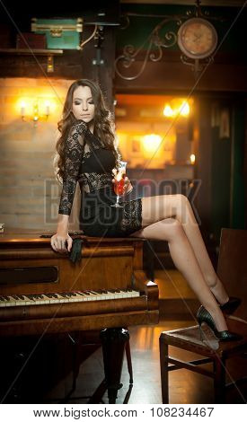 Young beautiful brunette woman in elegant black dress sitting provocatively on vintage piano