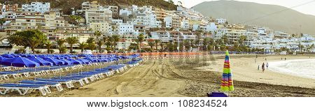 Sandy Beach With Blue Parasols And Sunbeds, Los Cristianos, Tenerife, Spain