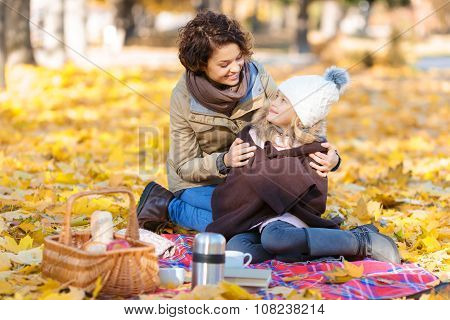 Happy mother sitting on the blanket with her daughter