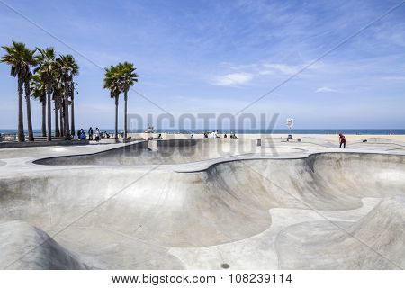 LOS ANGELES, CALIFORNIA, USA - June 20, 2014:  Concrete ramps and palm trees at the popular Venice beach skateboard park in Los Angeles, California.