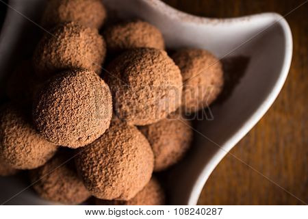 Chocolate Truffles In Bowl On Dark Wooden Table
